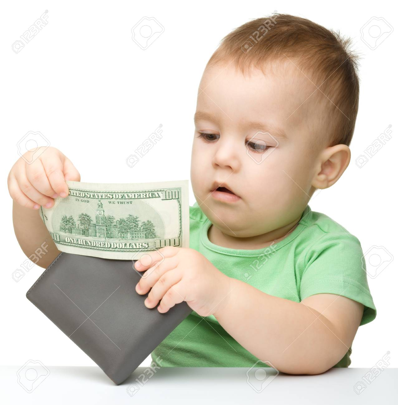 Cute little boy is playing with paper money - dollars, isolated over white Stock Photo - 12356897