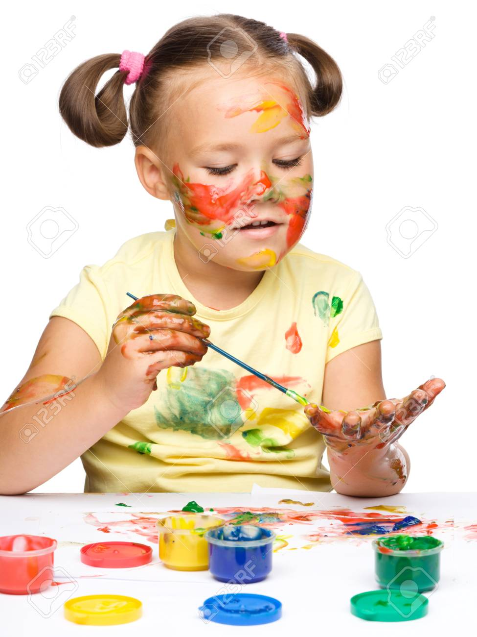 Portrait of a cute cheerful girl playing with paints, isolated over white Stock Photo - 15940422