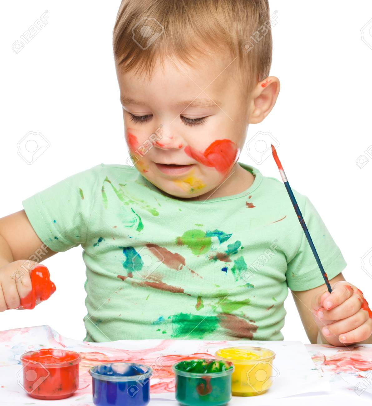 Portrait of a cute little boy playing with paints, isolated over white Stock Photo - 15940425
