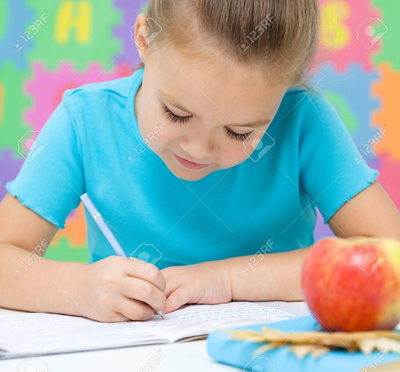 Cute little girl is writing using a pen in preschool Stock Photo - 16336130