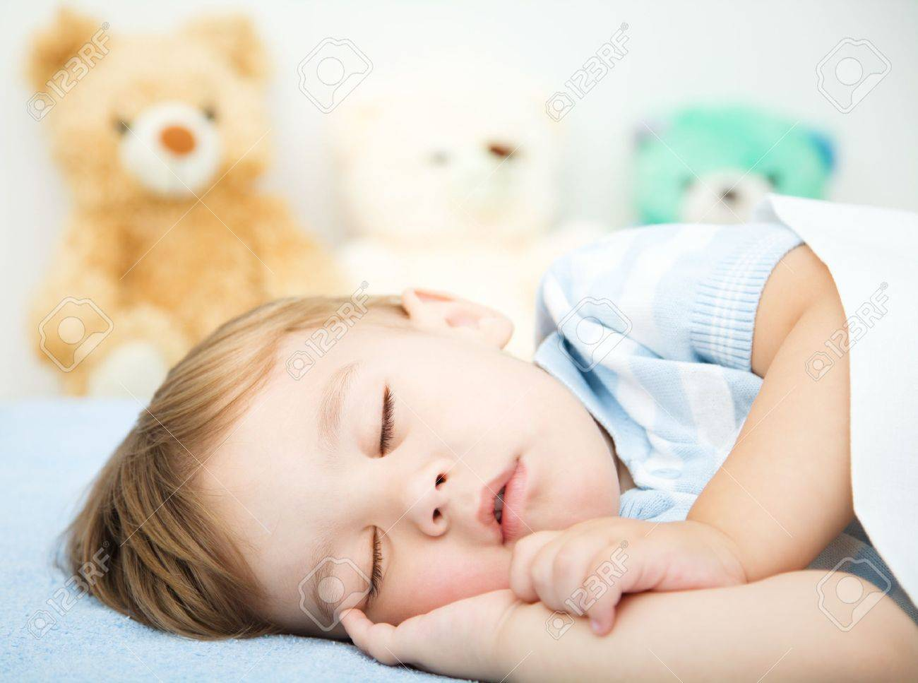 Cute little boy is sleeping in front of his teddy bears Stock Photo - 16792136