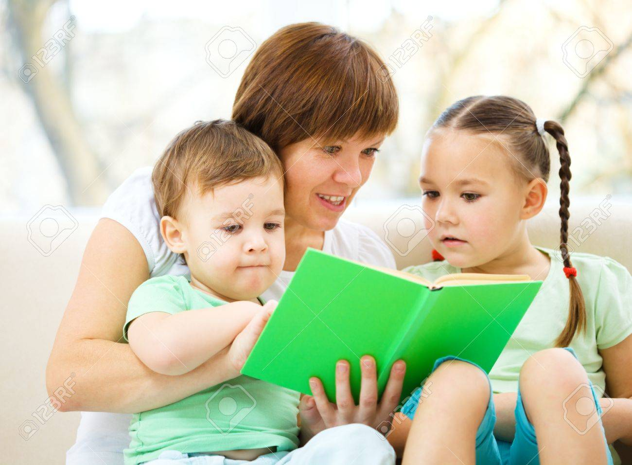 Family is reading book while sitting on a couch, indoor shoot Stock Photo - 16792284