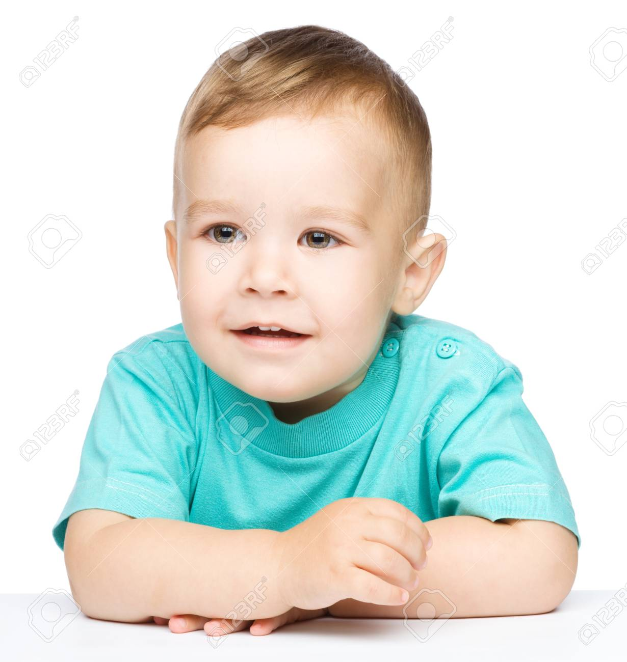 Portrait of a cute little boy sitting at table, isolated over white Stock Photo - 17055224