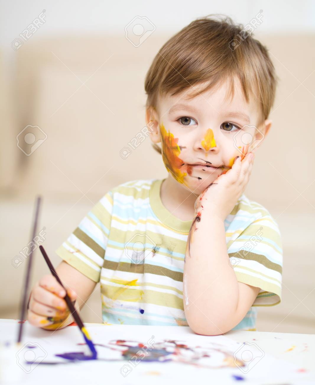 Portrait of a cute little boy messily playing with paints Stock Photo - 17160592