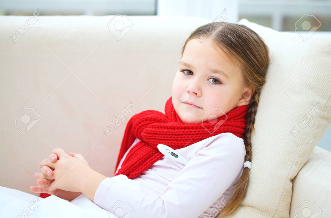Ill little girl is laying on sofa with thermometer under her arm Stock Photo - 17412178