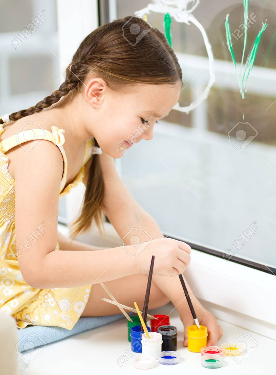 Portrait of a cute cheerful girl playing with paints on window Stock Photo - 17886757
