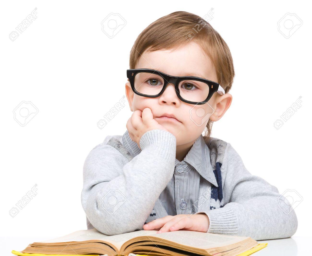 a5339bfb5514cf Schattige kleine kind te spelen met boek en bril terwijl zittend aan tafel