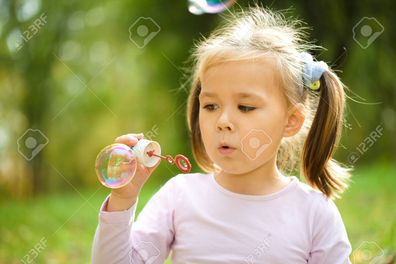 cute little girl is blowing a soap bubbles stock photo picture and