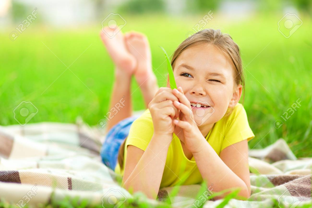 Portrait of a little girl laying on green grass, outdoor shoot Stock Photo - 30606911