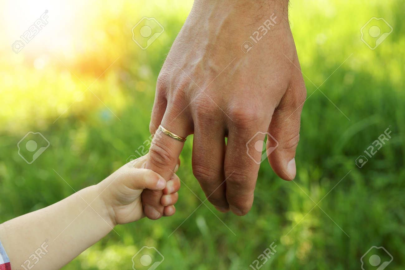 the parent holding the child's hand with a happy background - 168506843