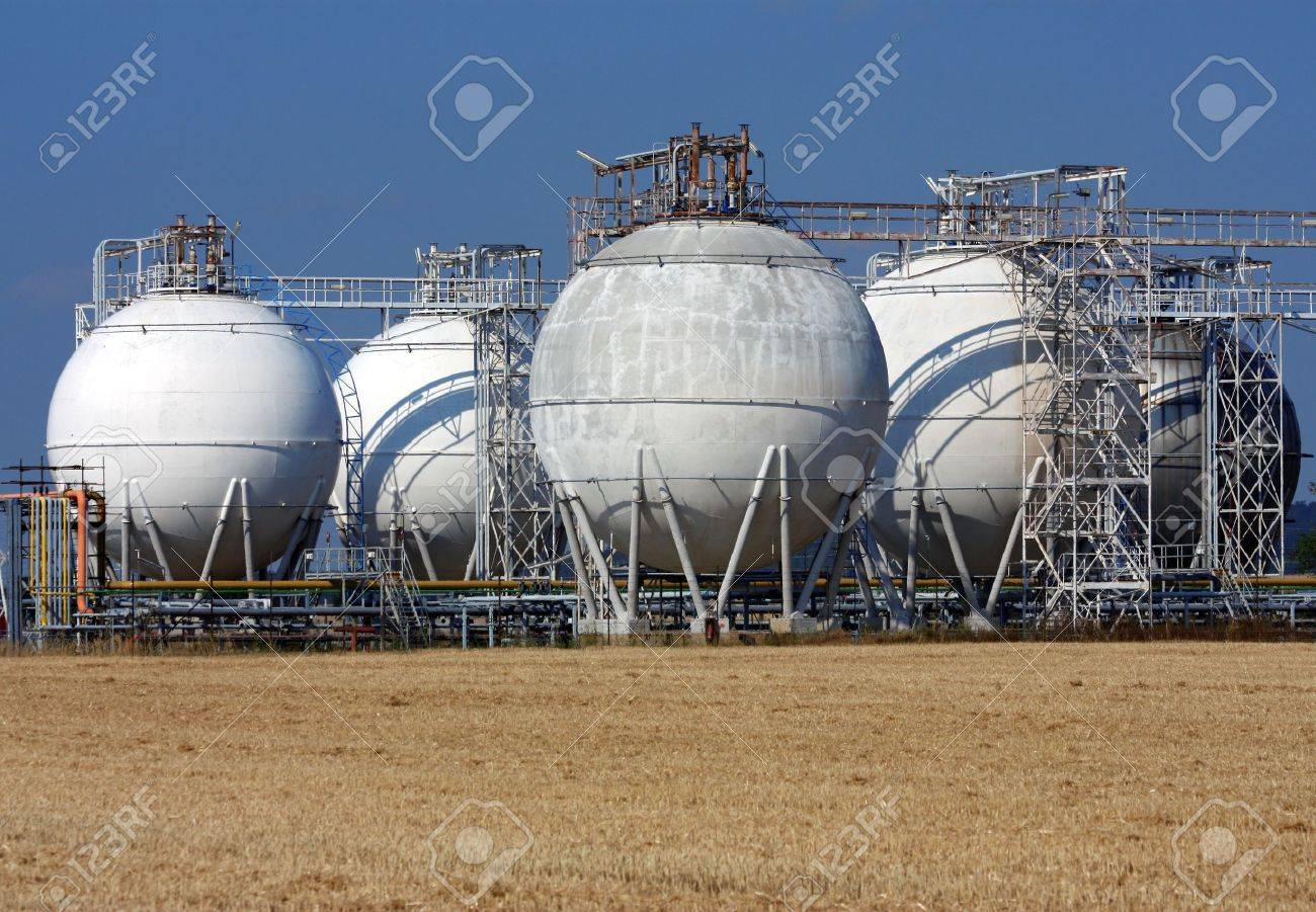 white rounded oil tanks and agriculture field Stock Photo - 8429861