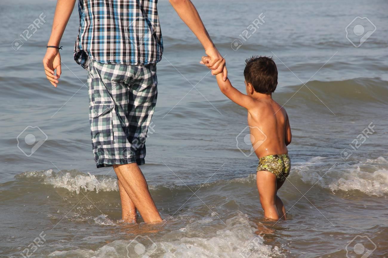 father leading son in sea Stock Photo - 11094729