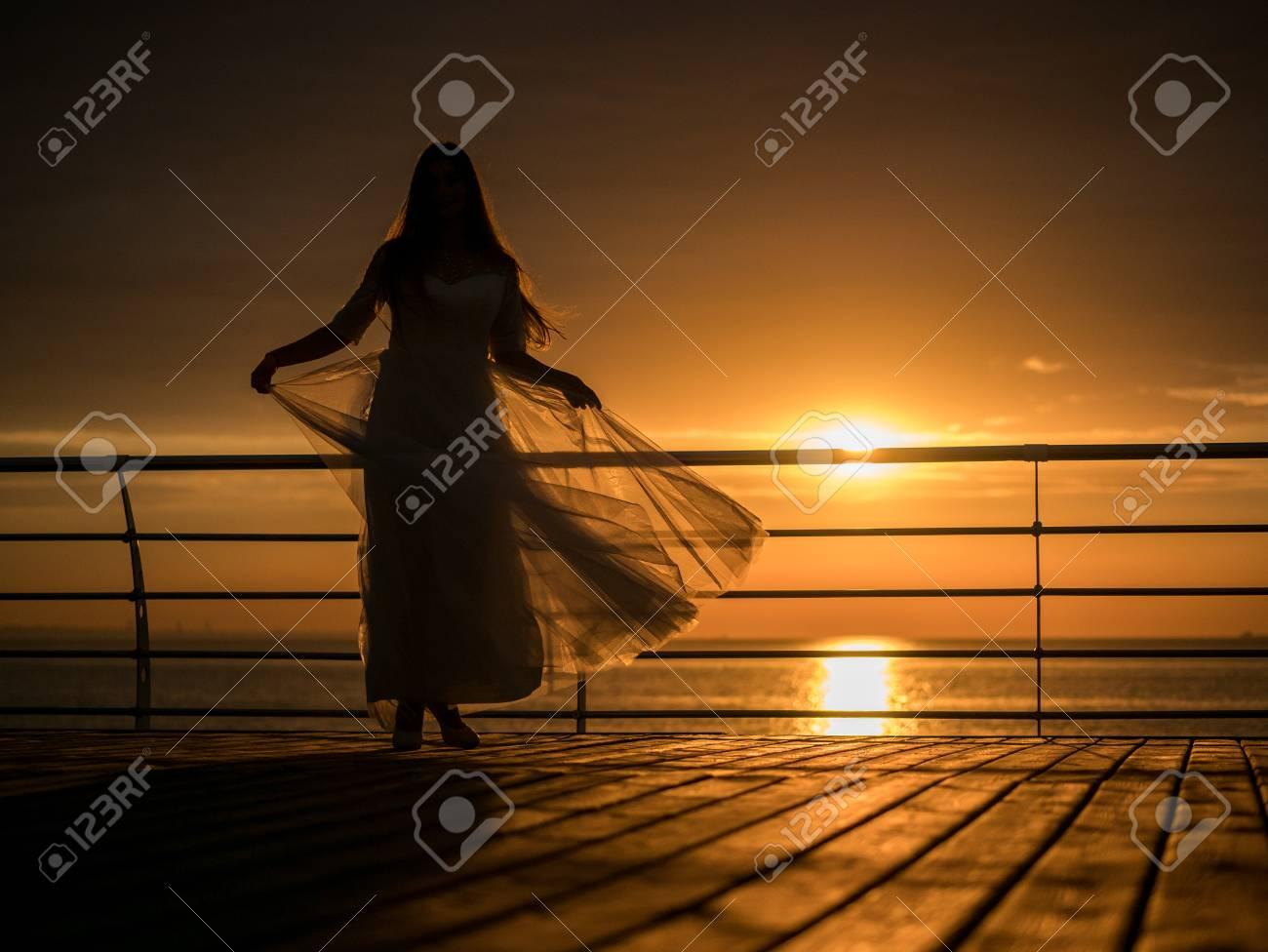 c7b335c2ca0e Siluetta della ragazza di bellezza sulla priorità bassa del cielo in un  vestito bianco vicino al mare. bella sposa