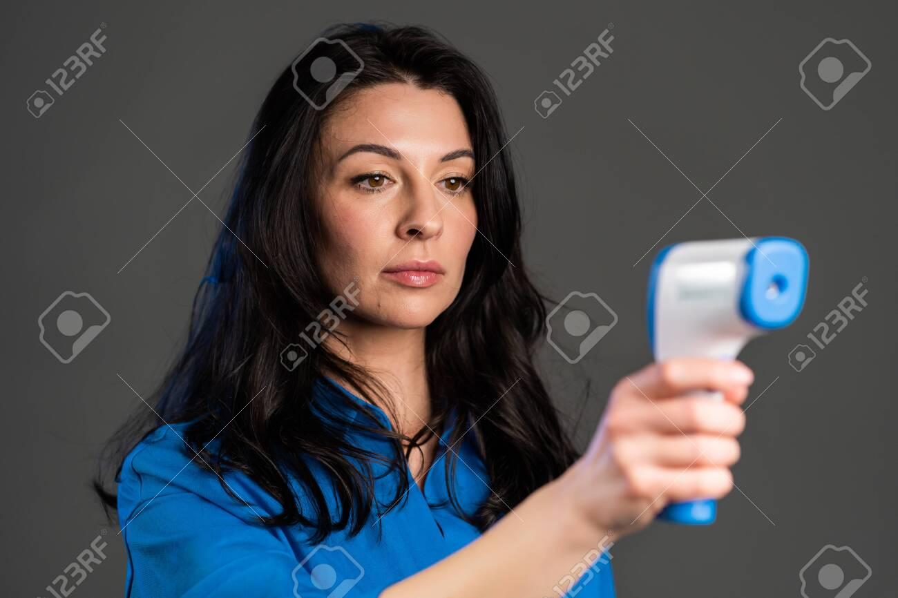 Beautiful Adult Woman Uses An Electronic Thermometer To Measure Temperature Flu Epidemic Covid 19 Coronavirus Fotos Retratos Imagenes Y Fotografia De Archivo Libres De Derecho Image 143618739