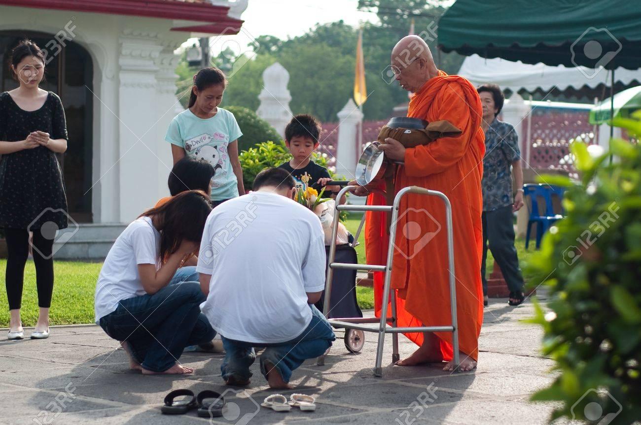 Wat Benchamabophit, Bangkok, Thailand - May 17, 2011 - Thai people give alms to a old Buddhist monk at  Wat Benchamabophit on Visakha Bucha day Stock Photo - 9538723