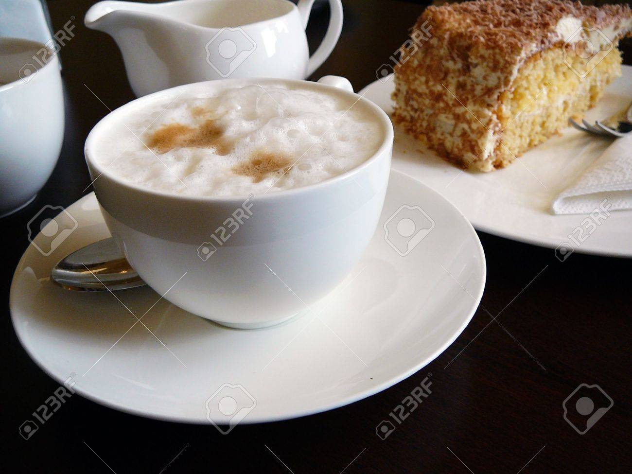 cappuccino and a fancy cake on a dark wooden table. in germany, this type of meal is often enjoyed in the afternoon, about 4 o'clock. Stock Photo - 772178