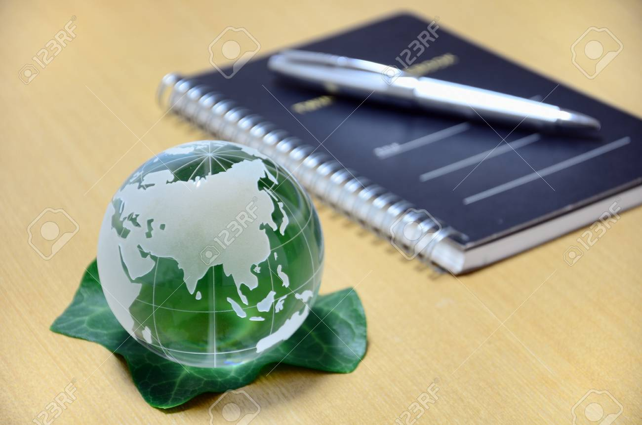 Green glass globe (Eurasian Continent). The green earth with a green leaf (ballpoint pen and notebook). Stock Photo - 11692509