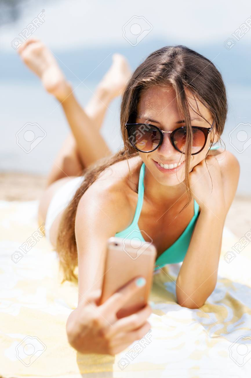 Sexy Girl With Sunglasses Taking Selfie While Sunbathing On A