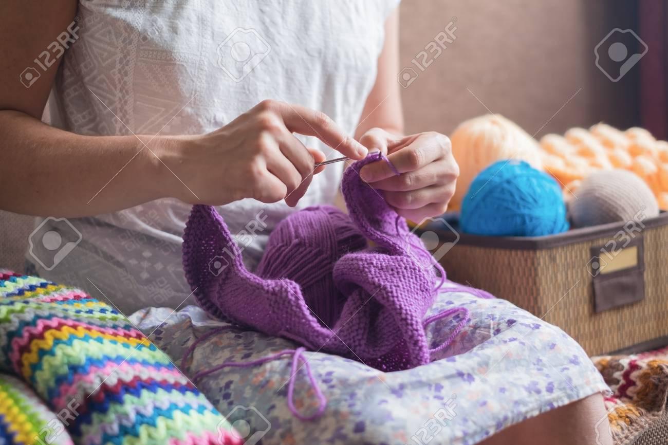 eb04c0ed1e76 Mujer caucásica tejidos de punto de ropa de lana. Sostener las agujas de  tejer en las manos