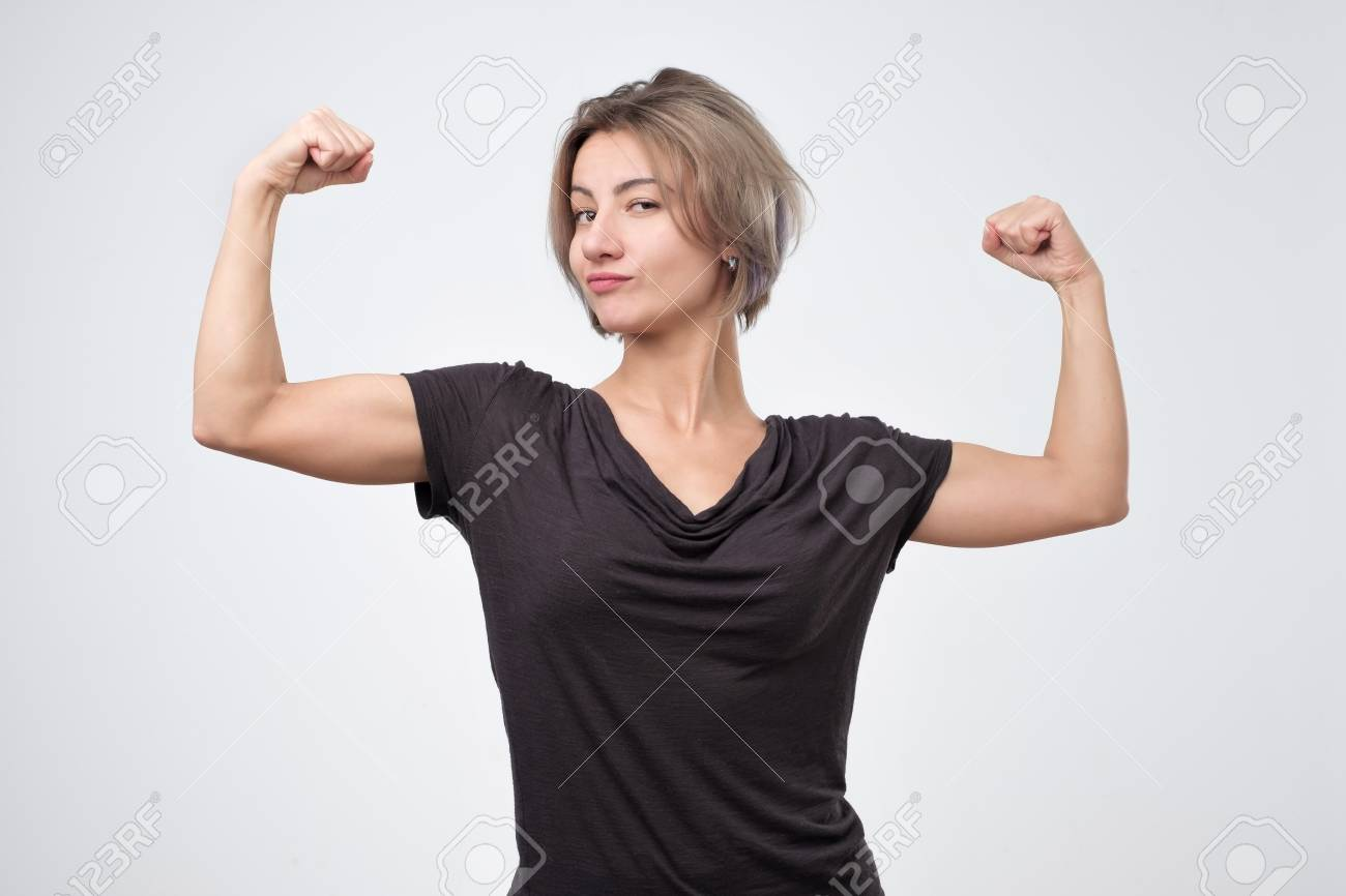 Happy young european woman showing her strong hand. I can do it concept - 114074343