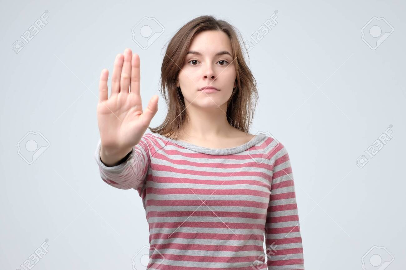 Serious young caucasian woman showing stop gesture with her hand. Studio shoot - 120202844