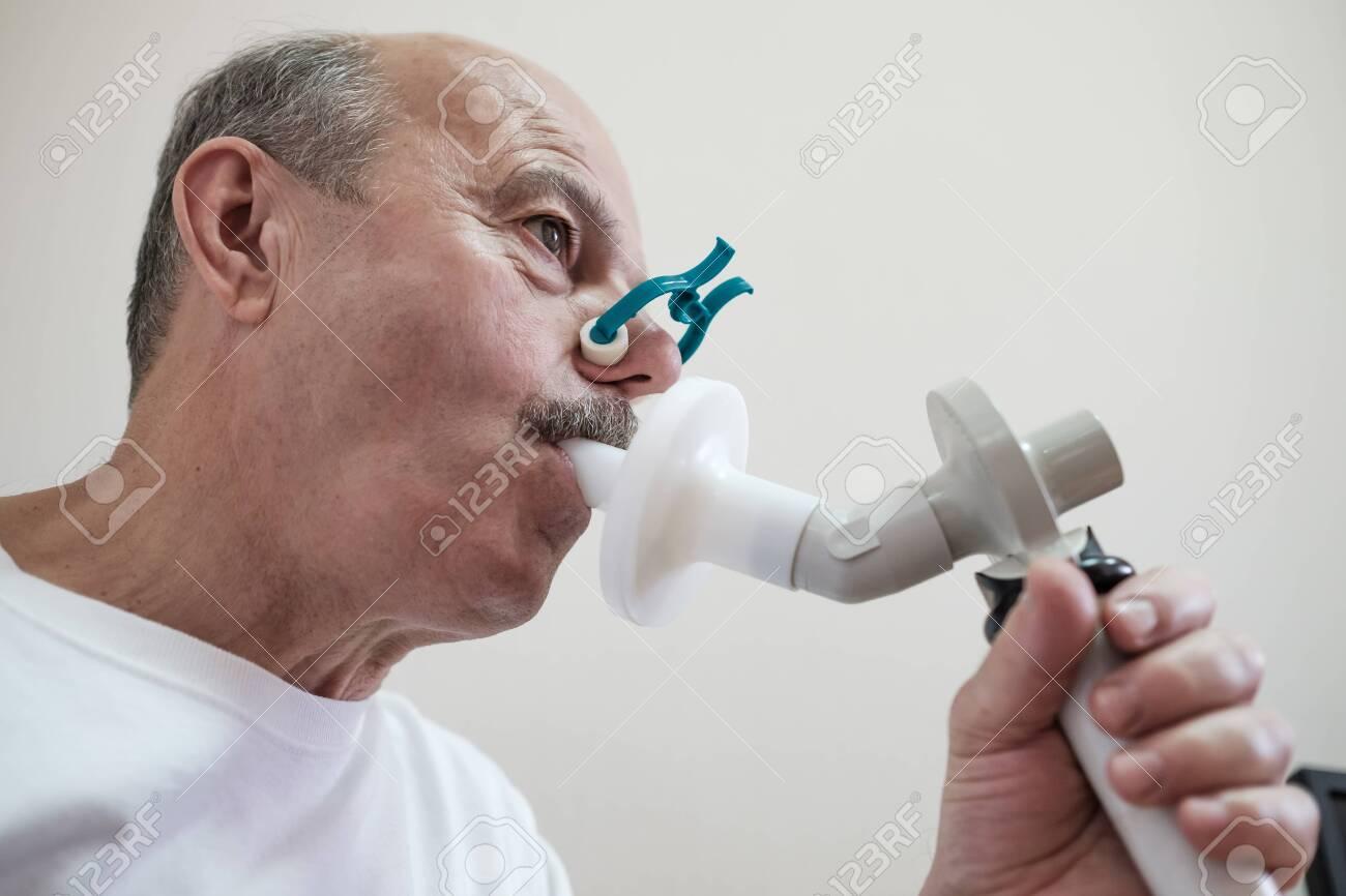 Senior hispanic man man testing breathing function by spirometry - 129849332