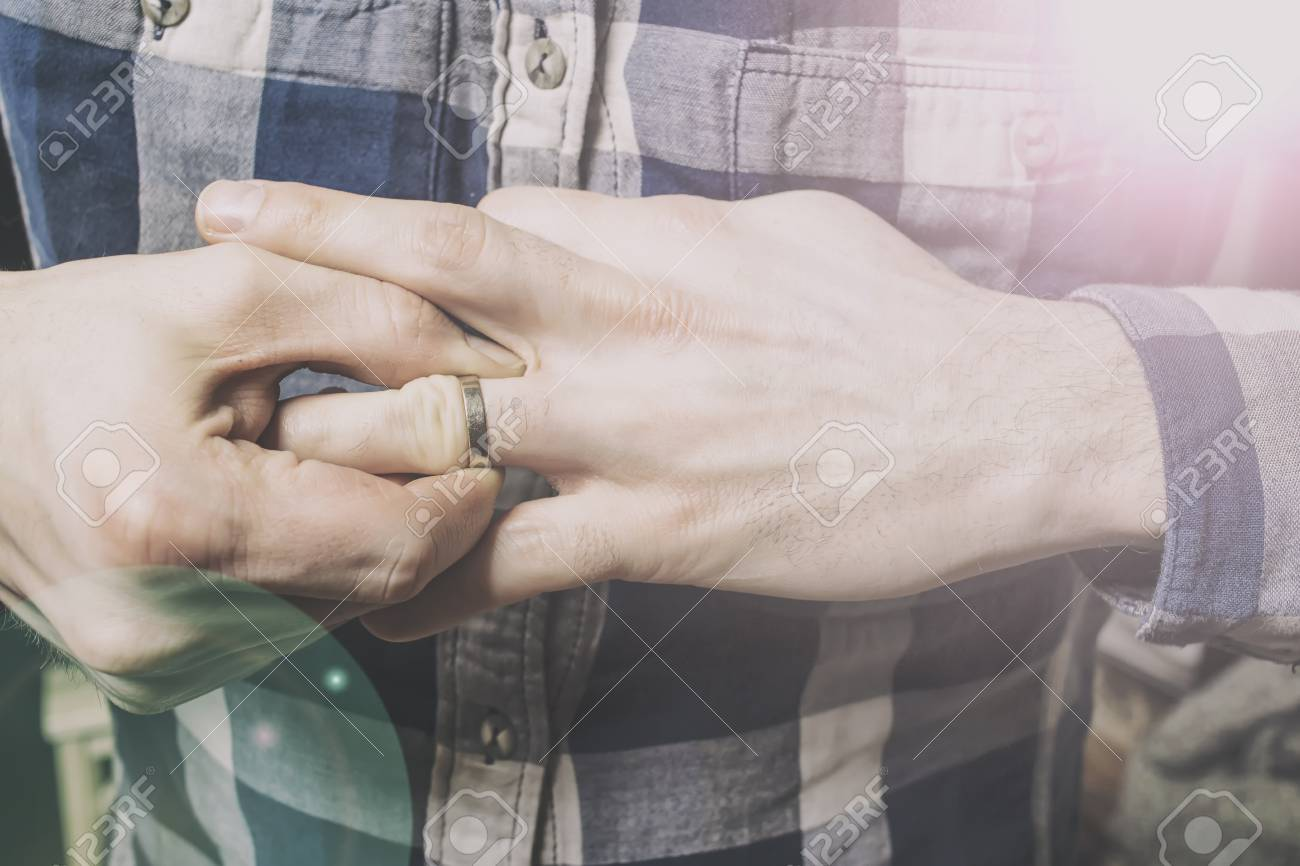 A Man Struggling To Remove Wedding Ring From His Finger Left