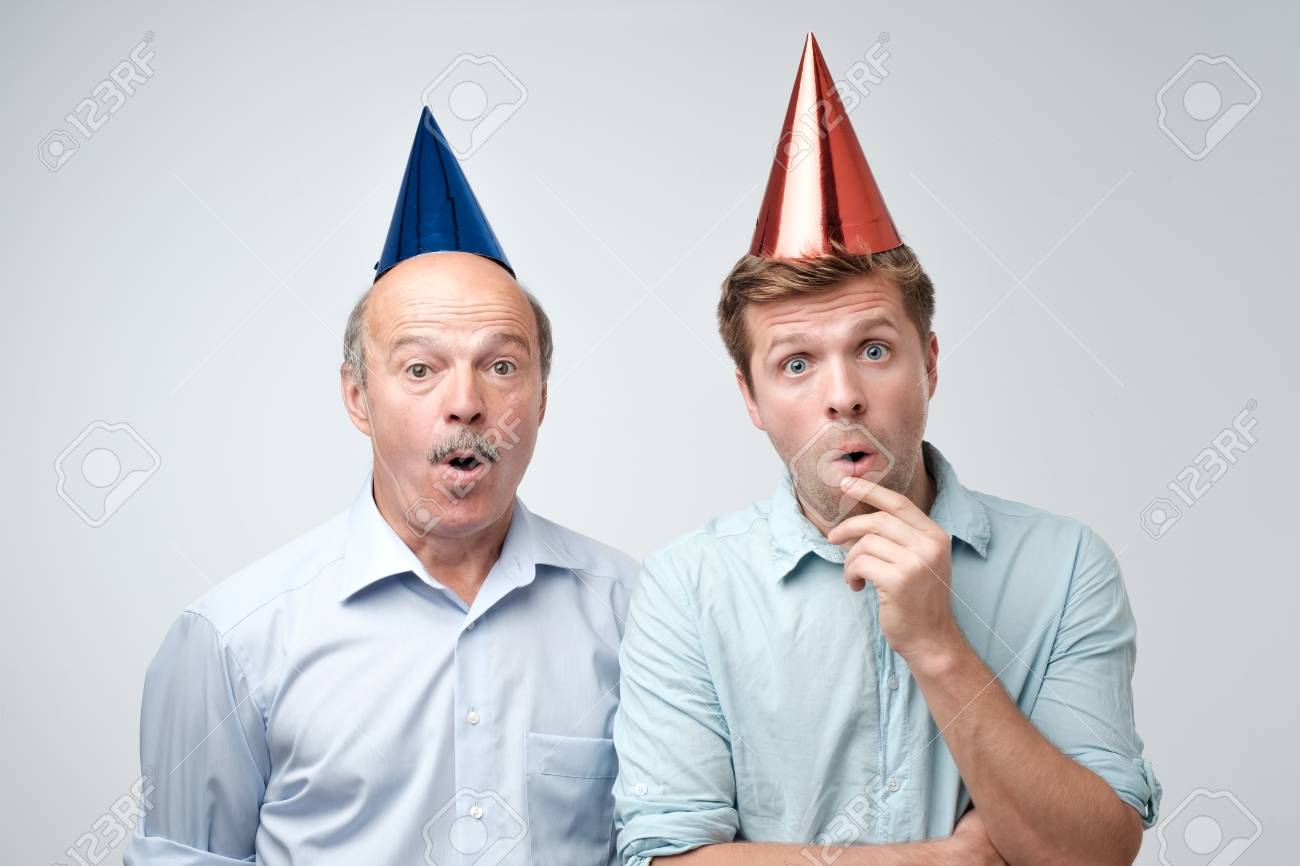 e11e73dc499 Photo curious shocked men standing in casual shirts and funny caps isolated  on pure background with