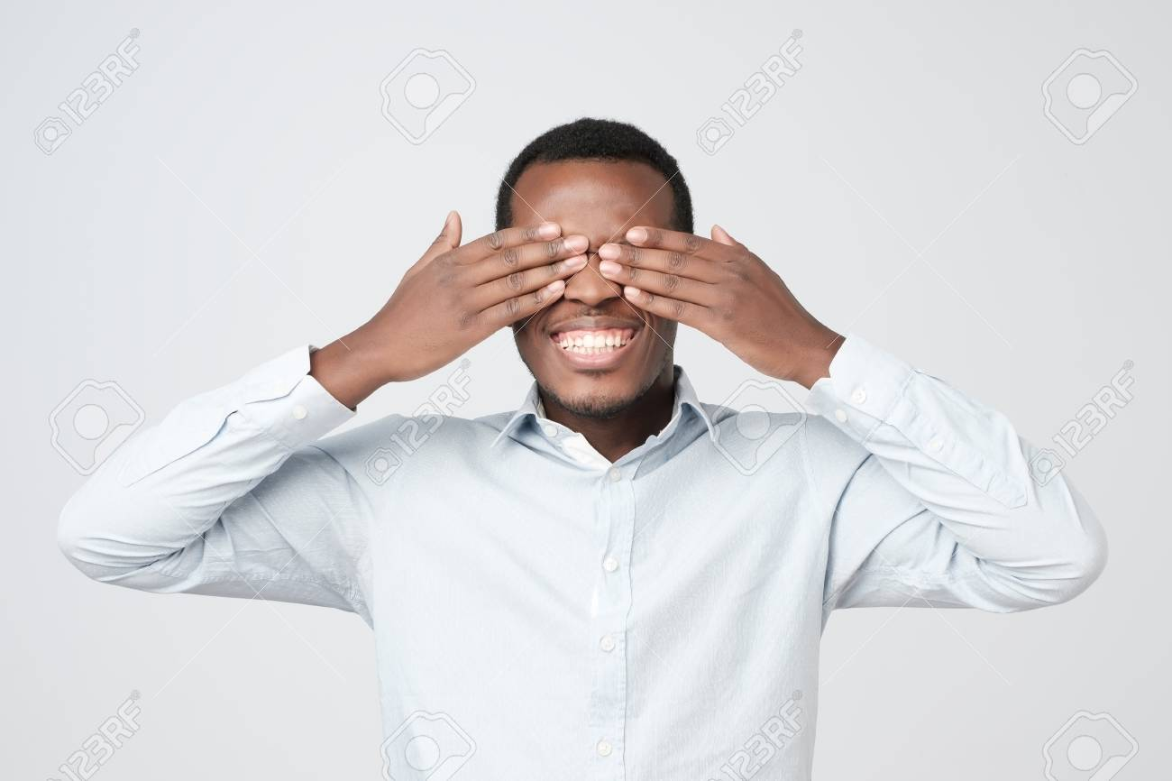 Young Happy African Man Covering Eyes With Hands Waiting For