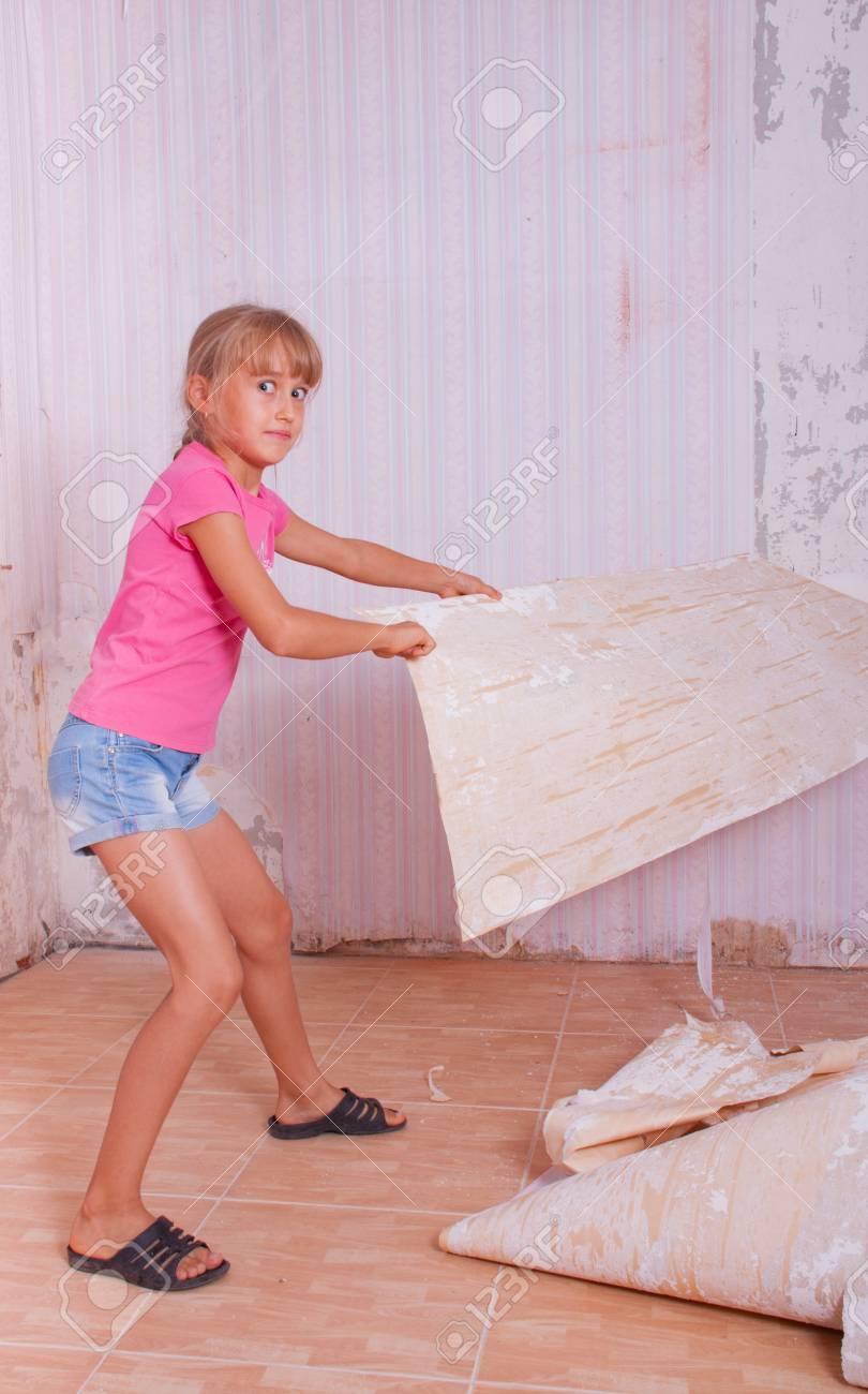 女の子が壁から古い壁紙を削除します の写真素材 画像素材 Image