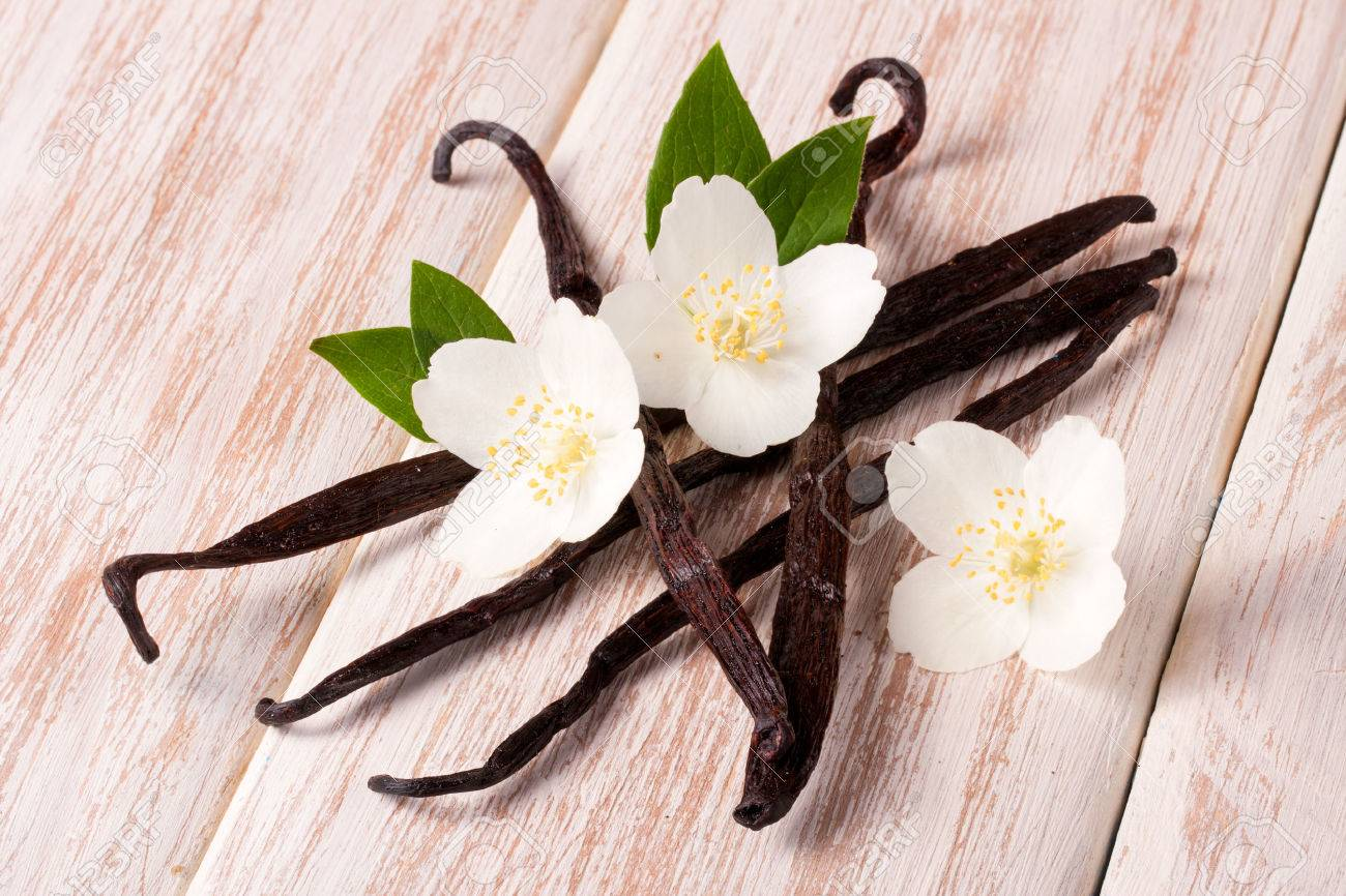 Vanilla sticks with flower and leaf on a white wooden background. - 82670242