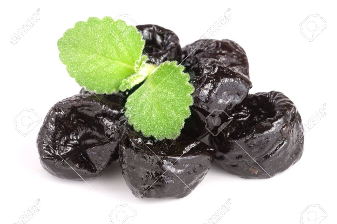 heap of dried plums or prunes with a mint leaf isolated on white background. - 83068992