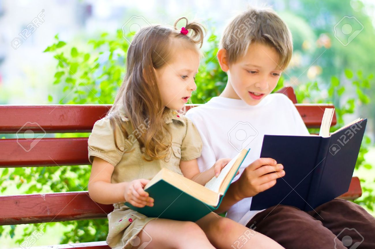 portrait of cute kids sitting in the park and reading interesting