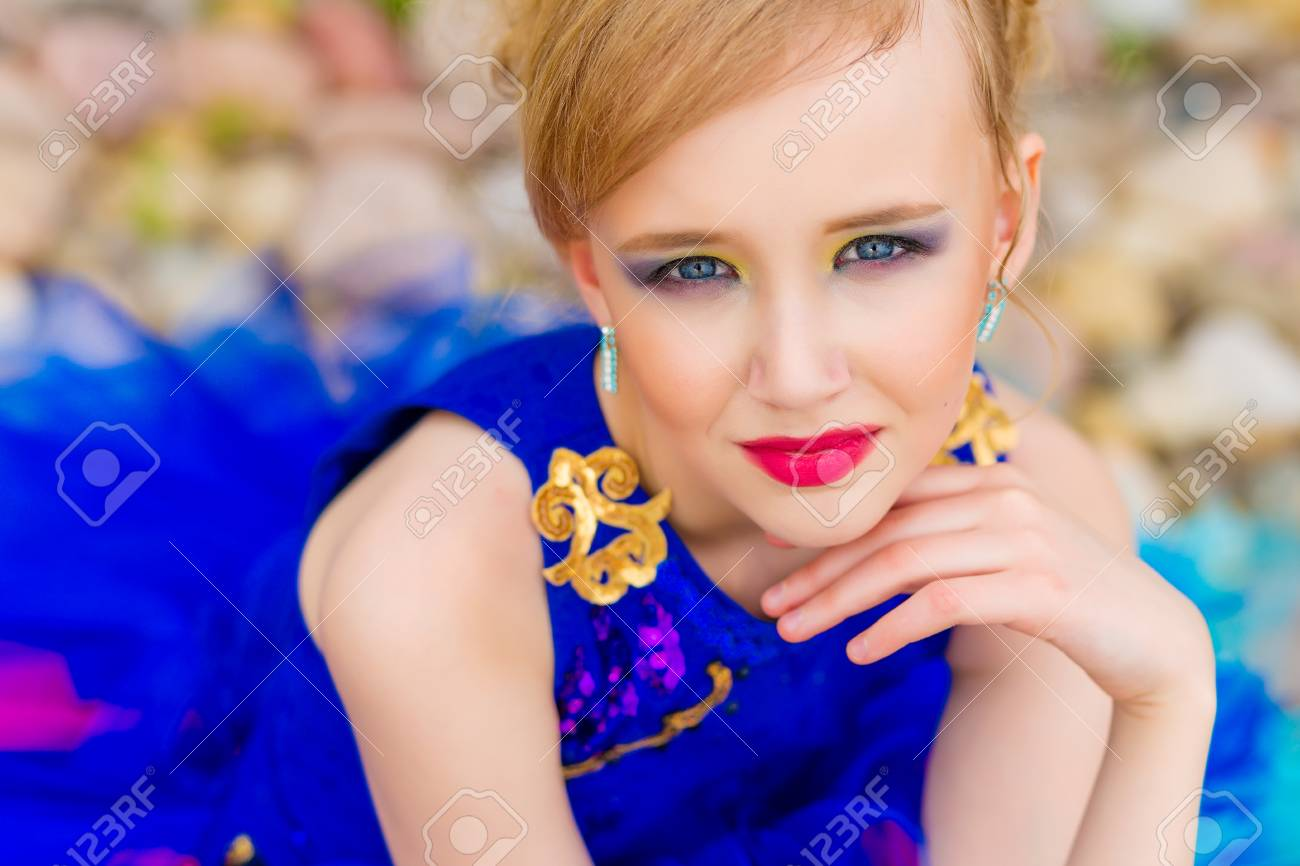 portrait of a beautiful cute girl with makeup in a blue dress stock