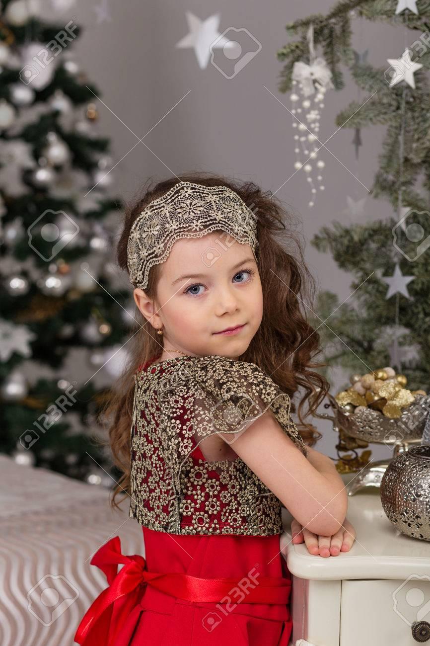 bd8c044fb Foto de archivo - Niña hermosa en un vestido de noche rojo del árbol de  Navidad. Chica de rojo en las decoraciones de Navidad. Niño lindo en la cama