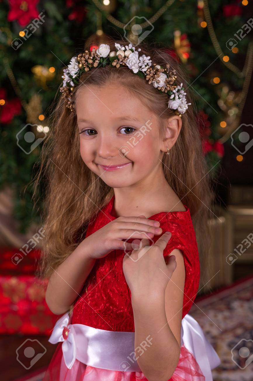 e6d388bc8 Little Beautiful Girl In Red Dress At The Christmas Tree. Portrait ...