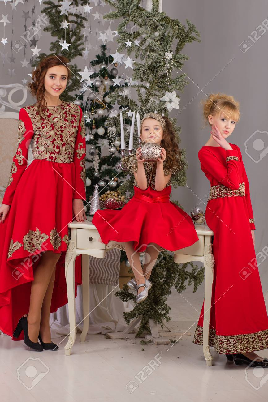 Christmas Evening Dresses.Three Girls In A Red Evening Dress The Christmas Tree Beautiful