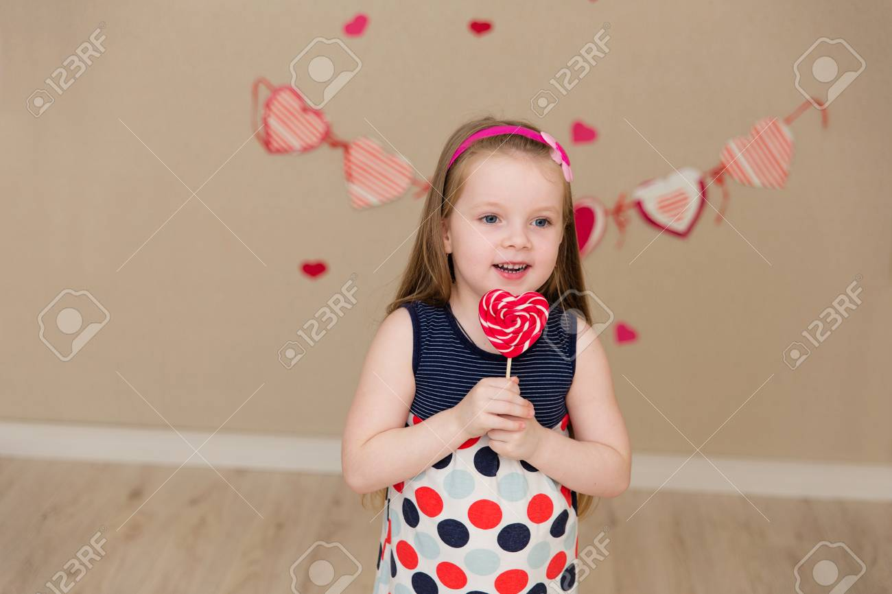 The Cute Girl With Blue Eyes With A Candy In The Hands Stock Photo ...