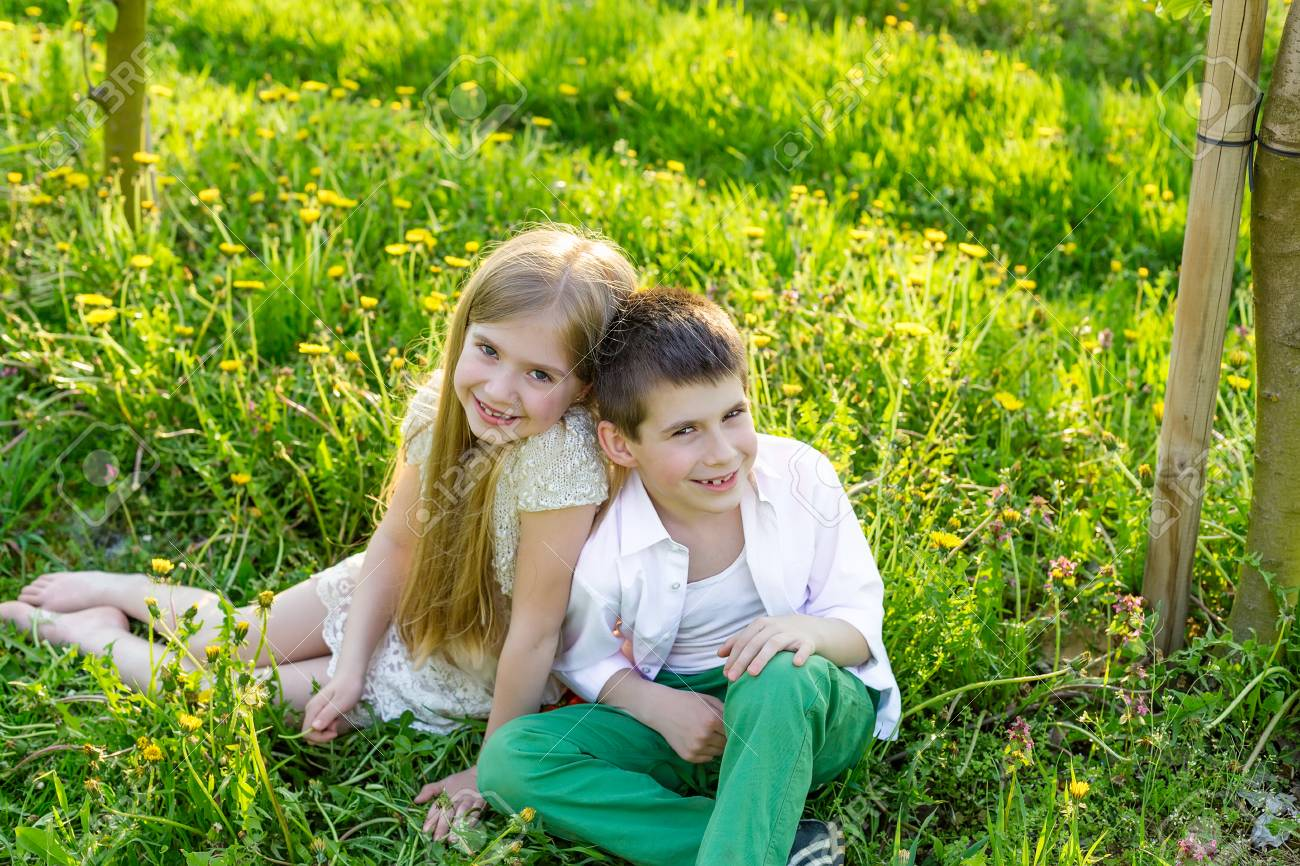 Sister and brother are resting in a blooming garden in the spring. Children have fun in the apple orchard before sunset. Beautiful happy boy and girl in the flowered garden in the rays of the setting sun - 75221721