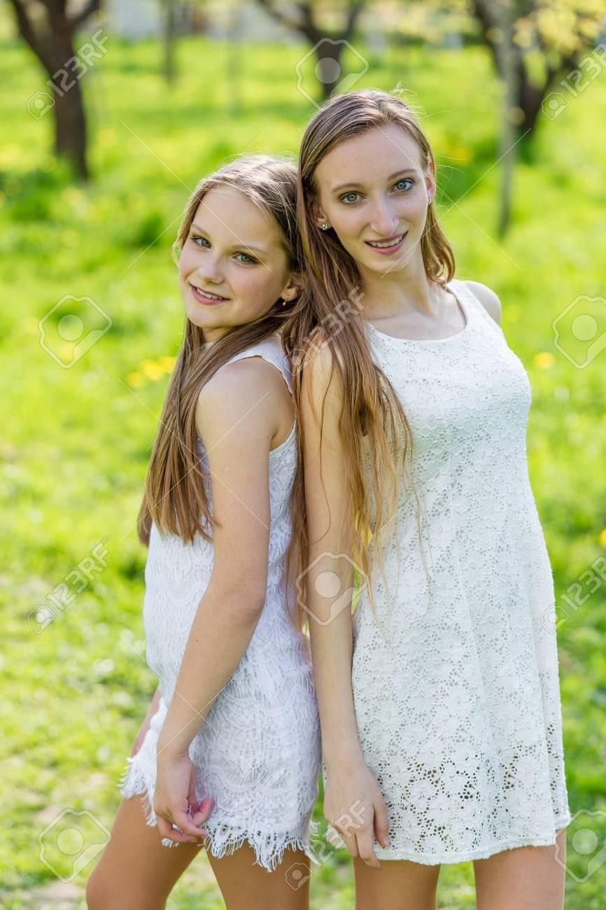 fe150c7266d9 Dos hermosas chicas jóvenes vestidas de blanco en el parque de verano