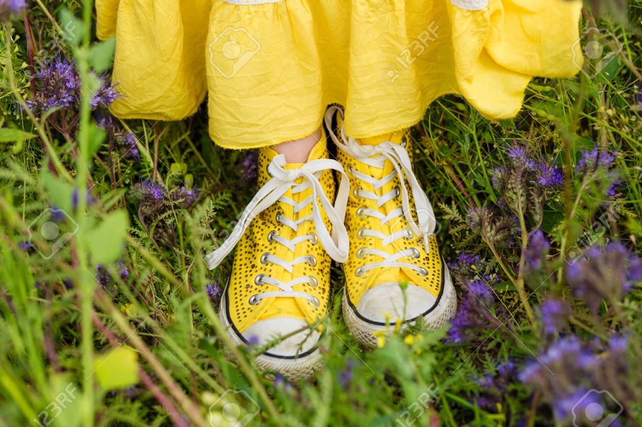 Yellow sneakers in the grass beautiful young girl in a yellow stock photo yellow sneakers in the grass beautiful young girl in a yellow dress in a blooming summer field girl in purple flowers outdoors in summer mightylinksfo