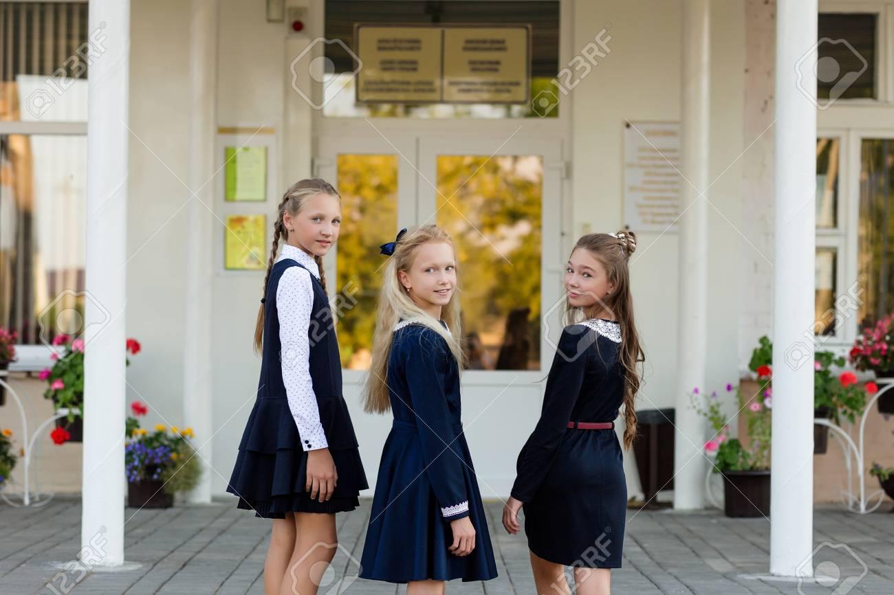a8c99c375 Colegialas en uniforme escolar que descansa en un descanso cerca del día de  la escuela.