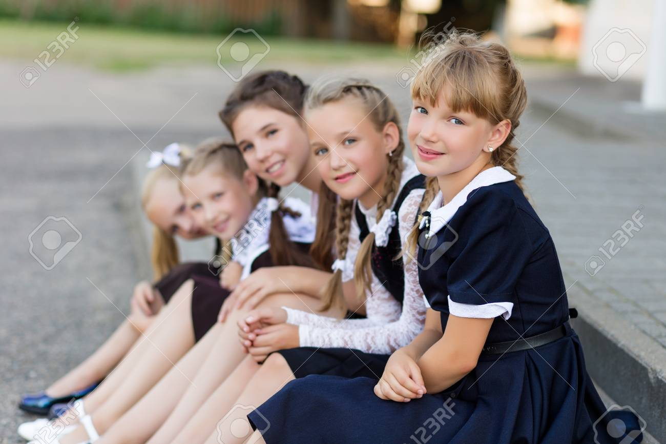 e8fa696da Colegialas en uniforme escolar descansan en un descanso cerca de la  escuela. Día de escuela