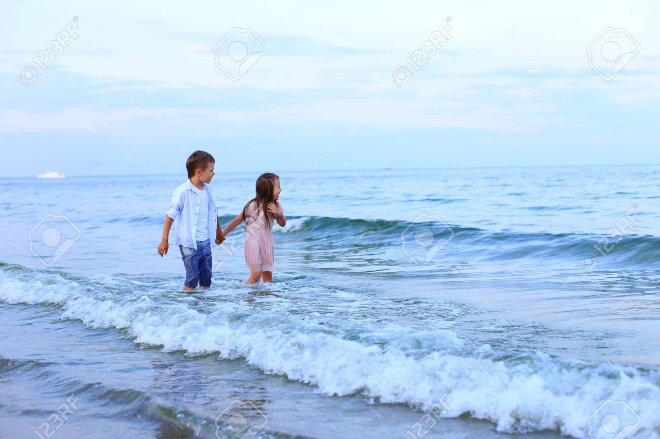 Two children run along the sea near the shore - 150765418