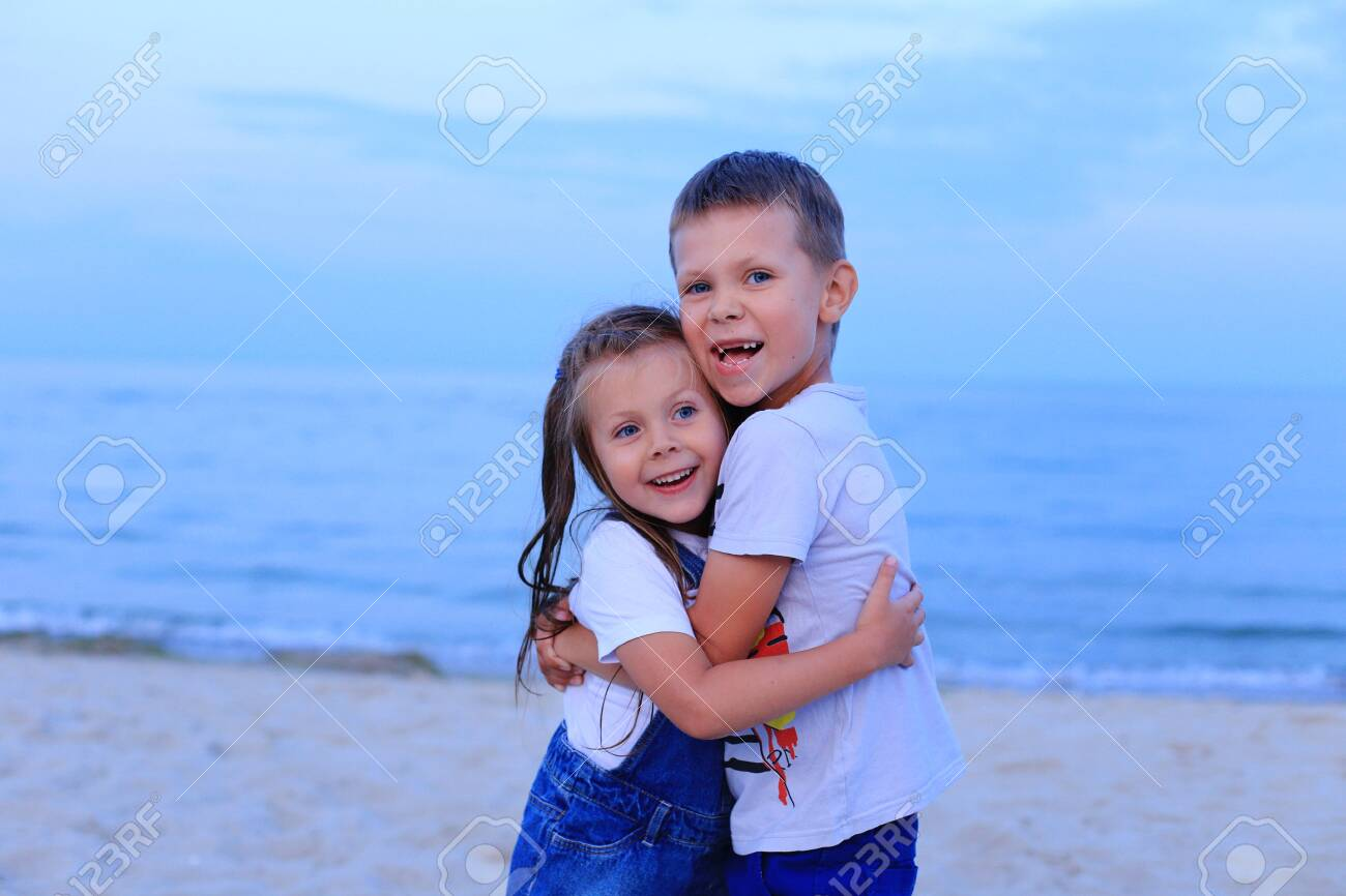 Two children stand on the seashore in summer. - 150825014