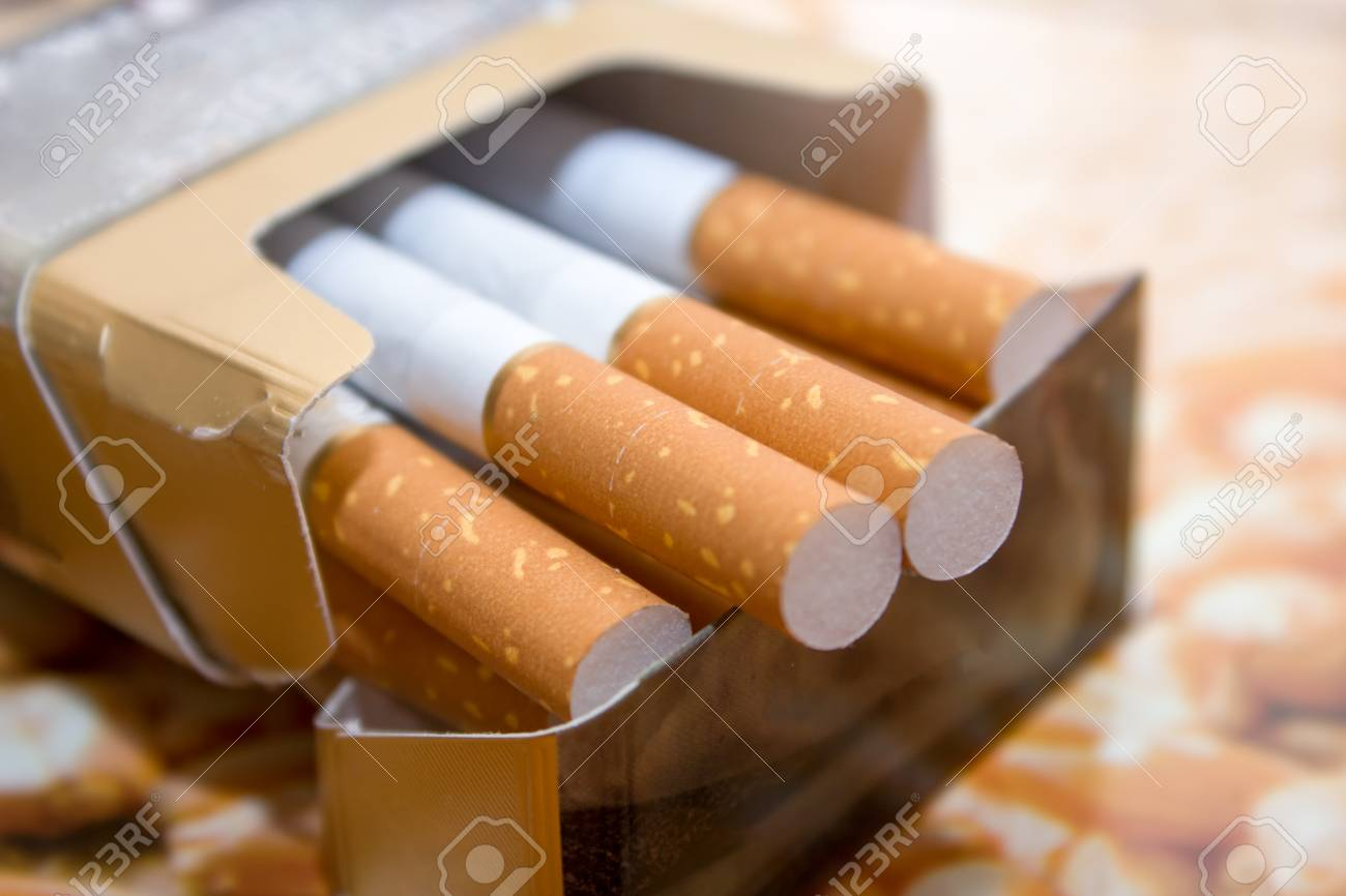 Cigarettes in a pack. Yellow filter. Harm to health. Bad habit. A pack of cigarettes on the table. open pack of cigarettes. - 121867451