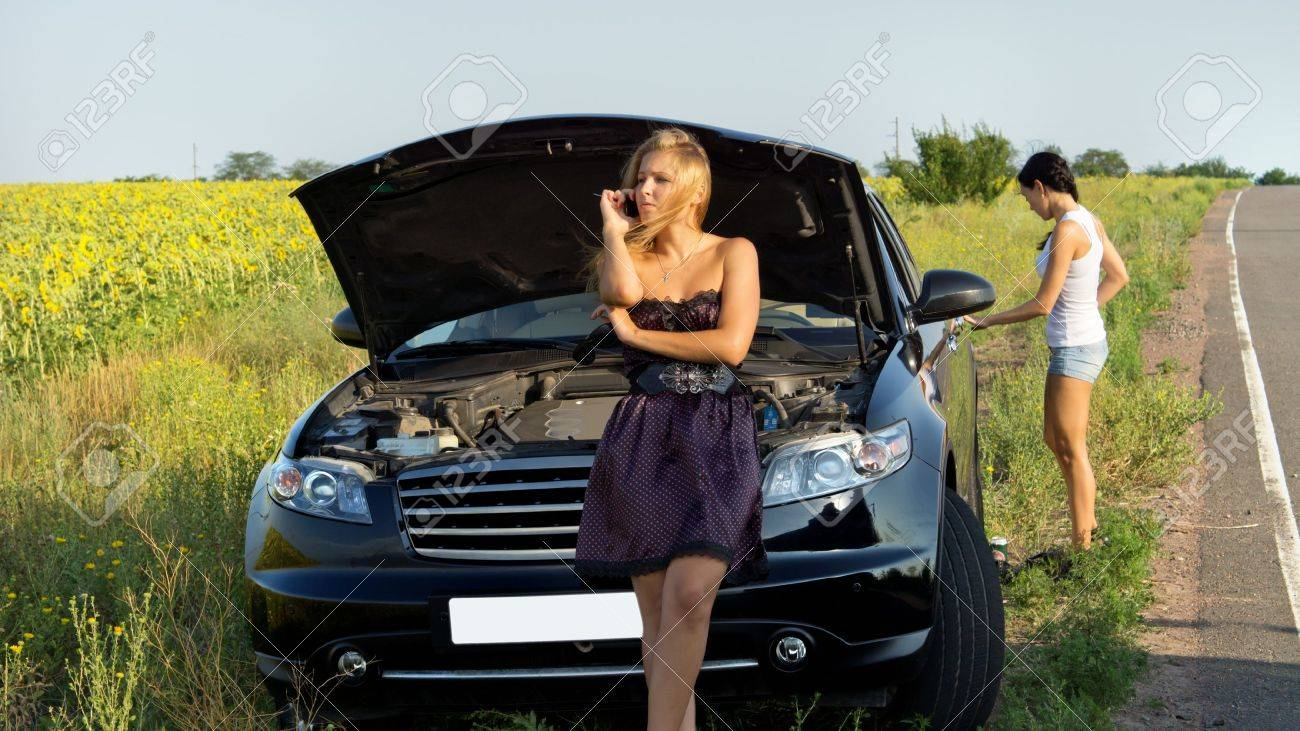 Woman phoning for help at a roadside breakdown as she sits on ther grille of the car with the bonnet raised - 14652837