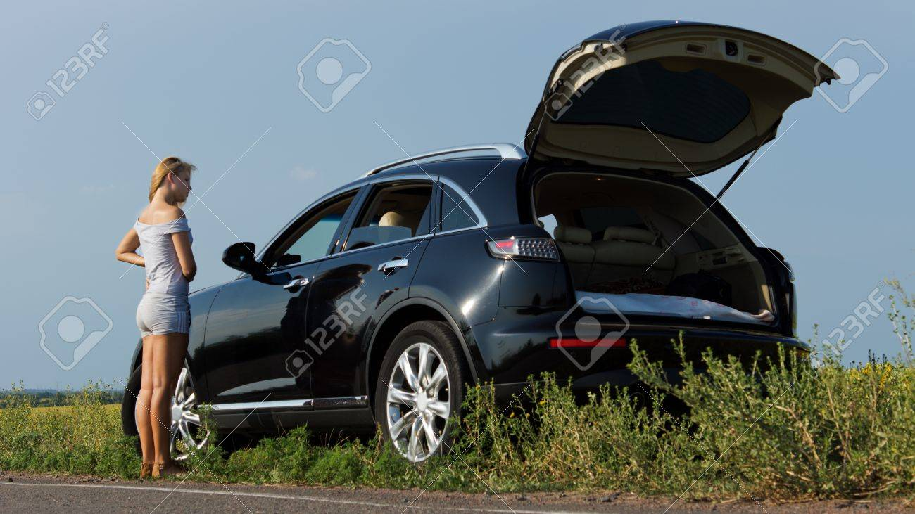 Low angle view of a woman standing alongside a car parked on the roadside with the hatch back open Stock Photo - 14747249