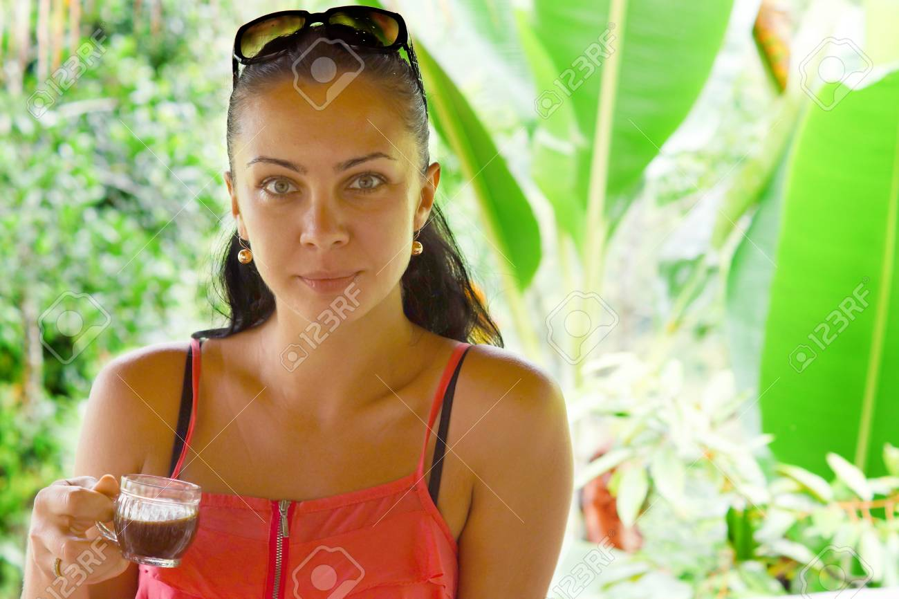 Portrait of a young woman drinking coffee with tropical background Stock Photo - 16562666
