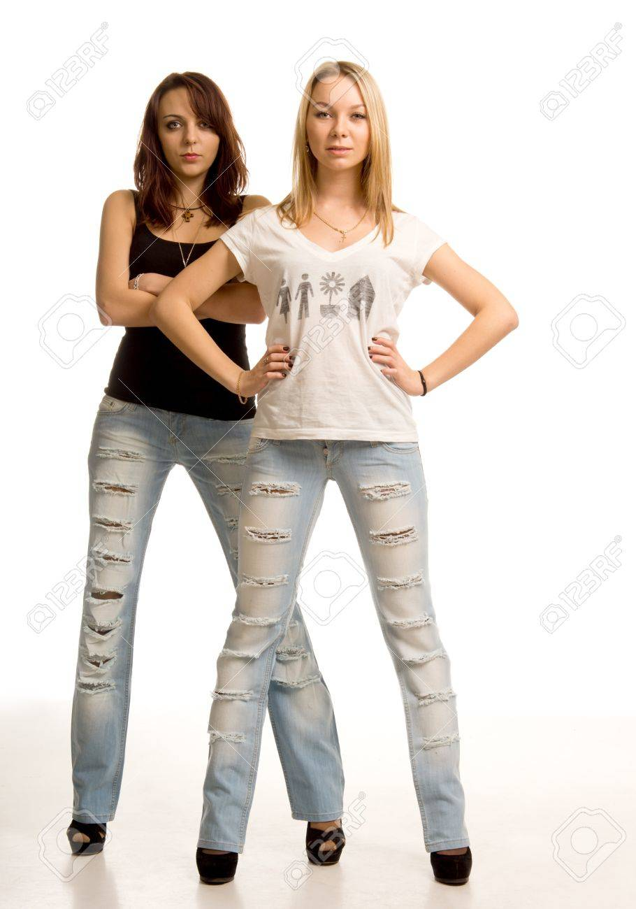 7d7ed7a207 Stock Photo - Two sexy young women with attitude standing side by side in skin  tight ragged designer jeans facing the camera with hands on hips or folded  ...